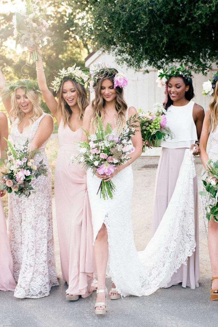 Blonde bride wearing Grace Loves Lace Gia Gown with bridesmaids holding bouquet