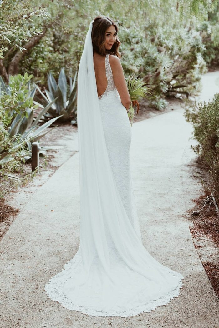 Back shot of bride wearing Grace Loves Lace Gia Gown and veil