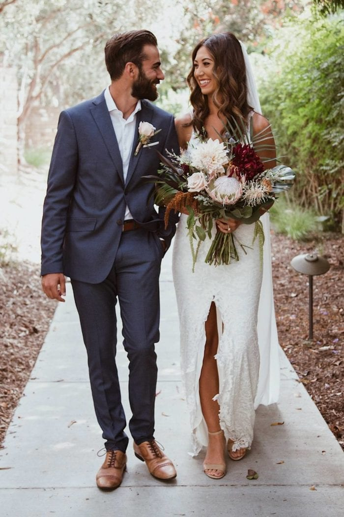 Brunette bride wearing Grace Loves Lace Gia Gown holding bouquet walking with groom