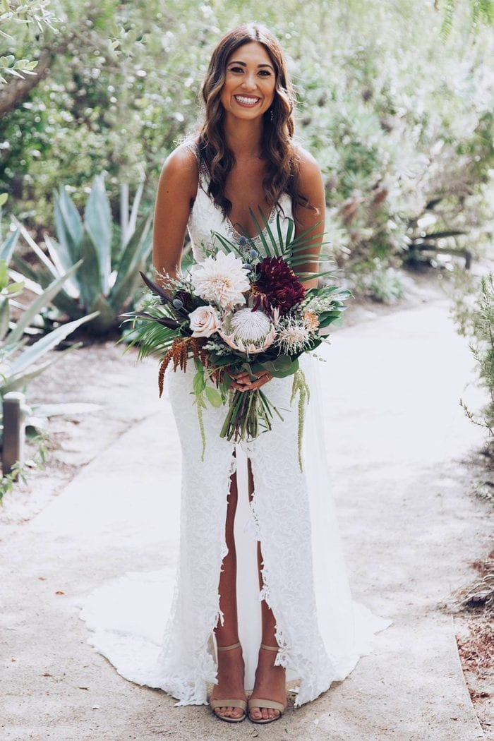 Brunette bride wearing Grace Loves Lace Gia Gown holding bouquet