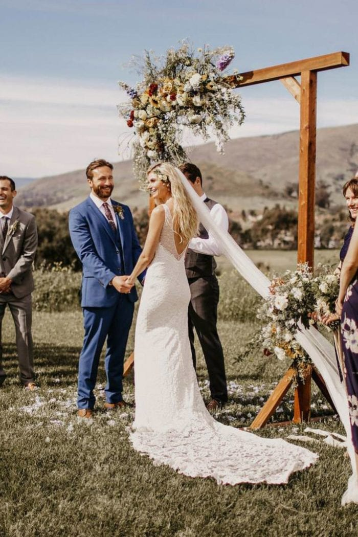 Blonde bride wearing Grace Loves Lace Gia Gown holding hands with groom during ceremony