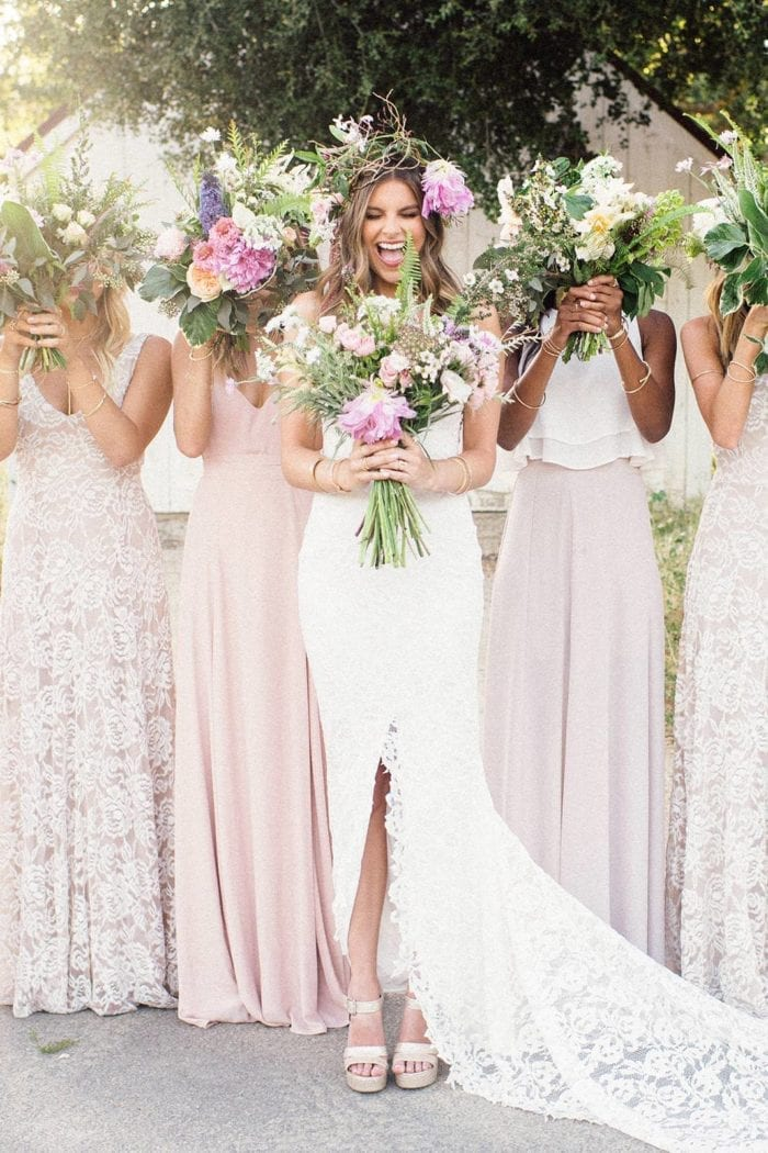 Blonde bride wearing Grace Loves Lace Gia Gown with bridesmaids holding bouquets