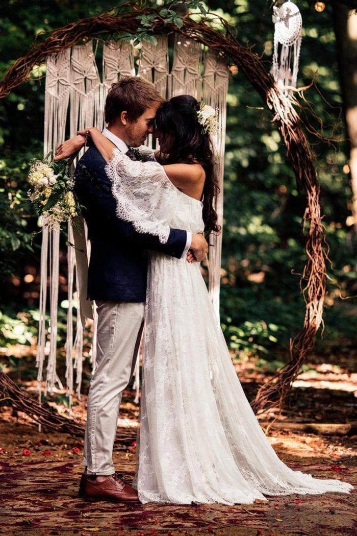Brunette bride wearing Grace Loves Lace Florence Gown in Ivory embracing groom in forest