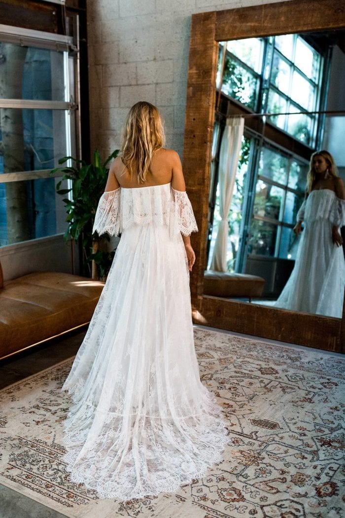 Back shot of blonde bride wearing Grace Loves Lace Florence Gown in Ivory in front of mirror