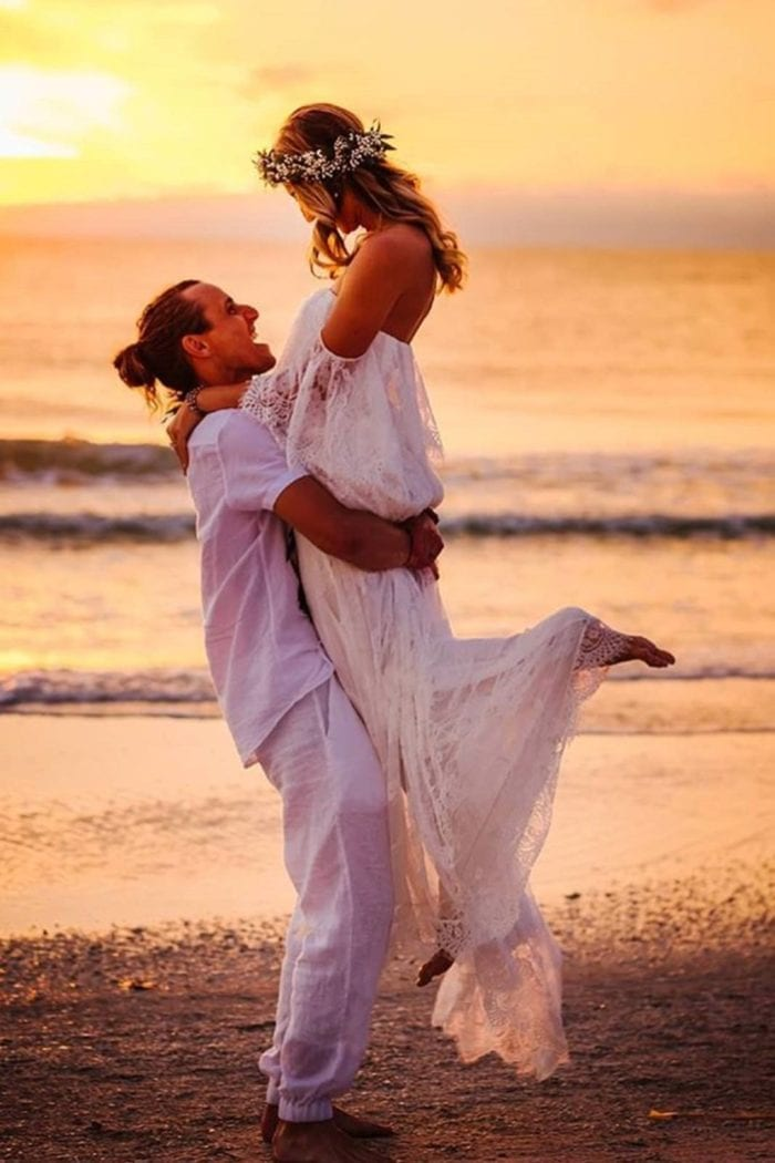Blonde bride wearing Grace Loves Lace Florence Gown in Ivory being held by groom on beach at sunset