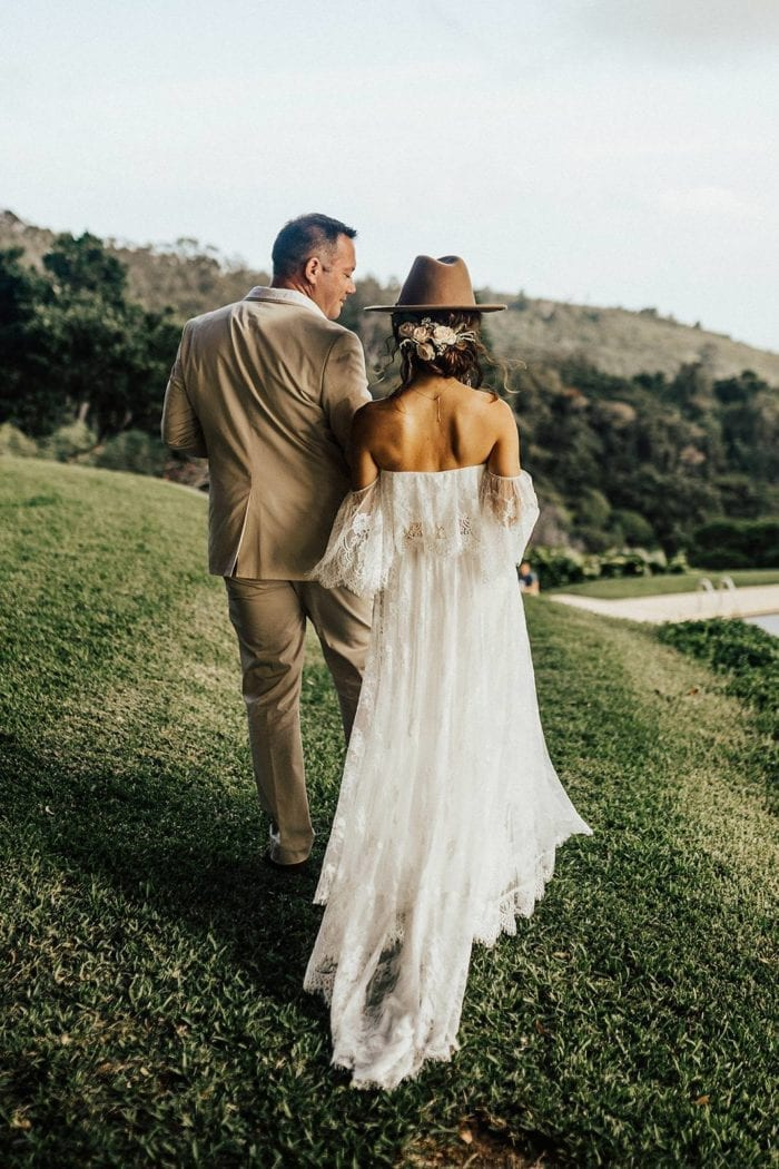 Blonde bride wearing Grace Loves Lace Florence Gown in Ivory and hat standing with groom on grassy hill