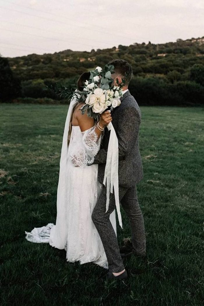Brunette bride wearing Grace Loves Lace Florence Gown in Ivory kissing groom behind bouquet in grassy field