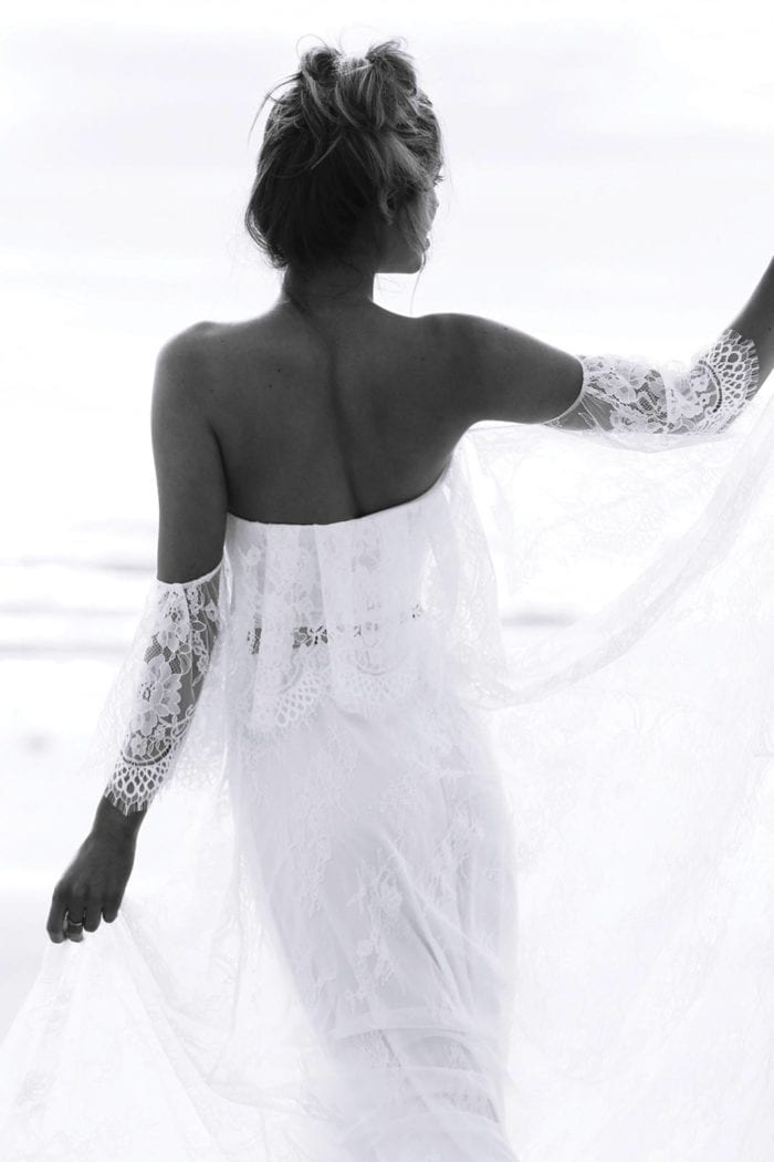 Black and white shot of bride wearing Grace Loves Lace Florence Gown in Ivory holding skirt in hands