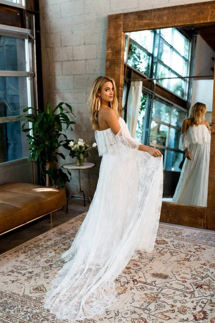 Blonde bride wearing Grace Loves Lace Florence Gown in Ivory looking over shoulder in front of mirror