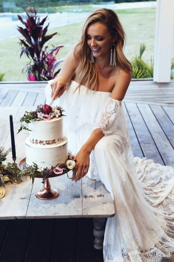 Blonde bride wearing Grace Loves Lace Florence Gown in Ivory sitting down cutting cake
