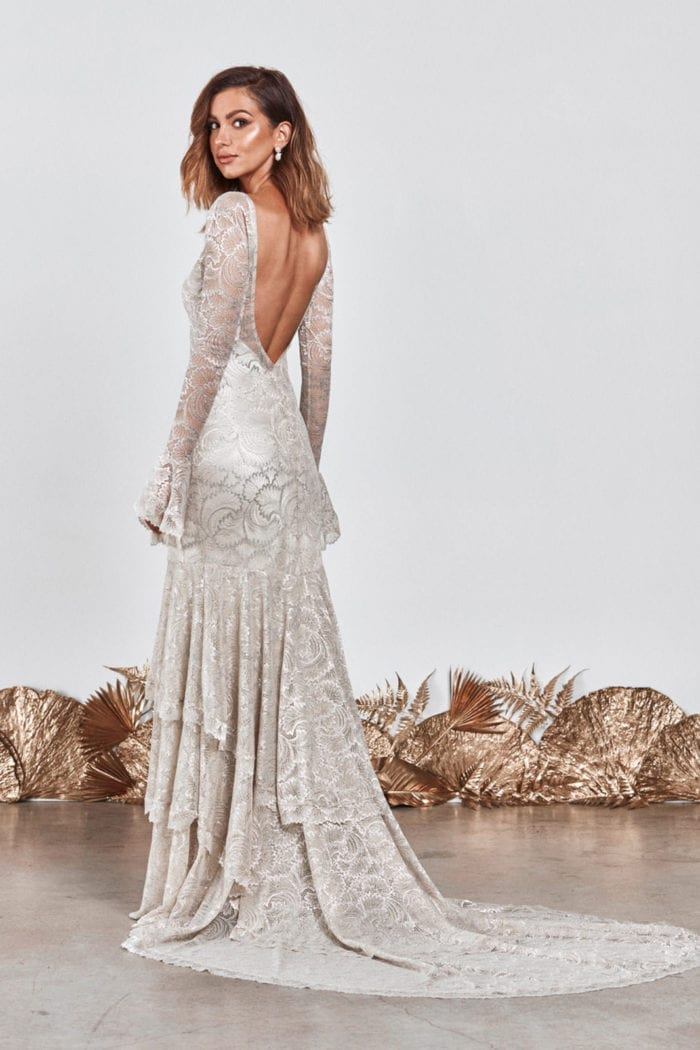 Back shot of bride wearing Grace Loves Lace Farrow Gown looking over shoulder