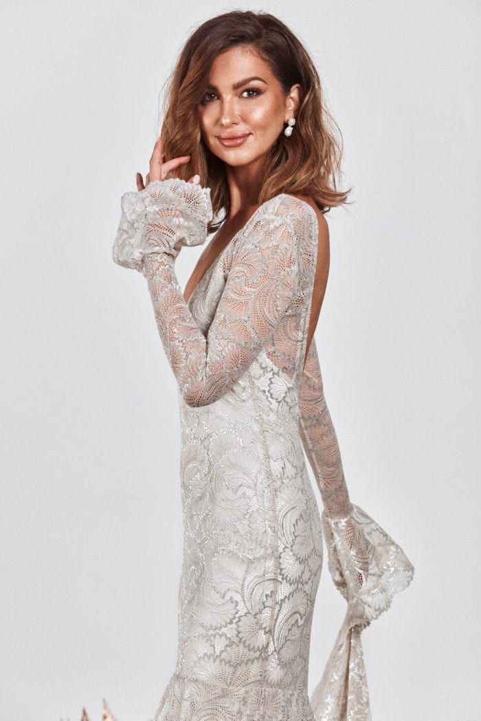 Brunette bride wearing Grace Loves Lace Farrow Gown holding train in one hand