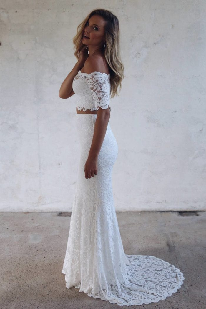 Blonde bride wearing Grace Loves Lace Everly Gown with hand on hair