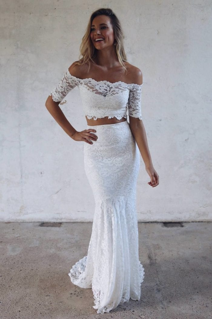 Blonde bride wearing Grace Loves Lace Everly Gown with hand on hip