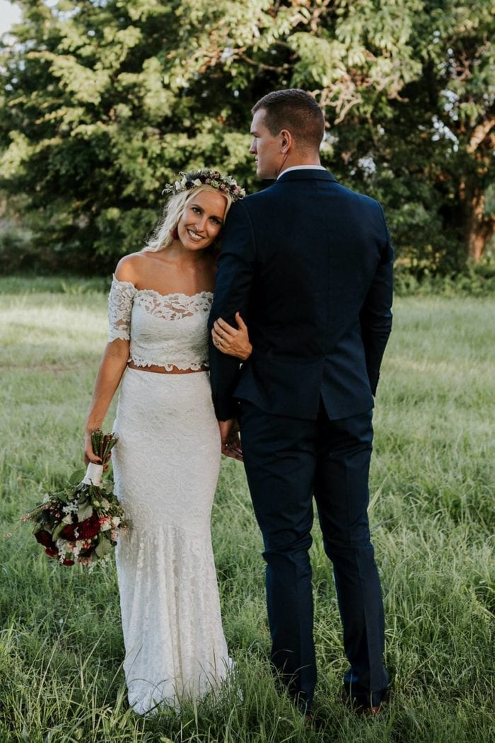 Blonde bride wearing Grace Loves Lace Everly Gown holding bouquet standing with groom