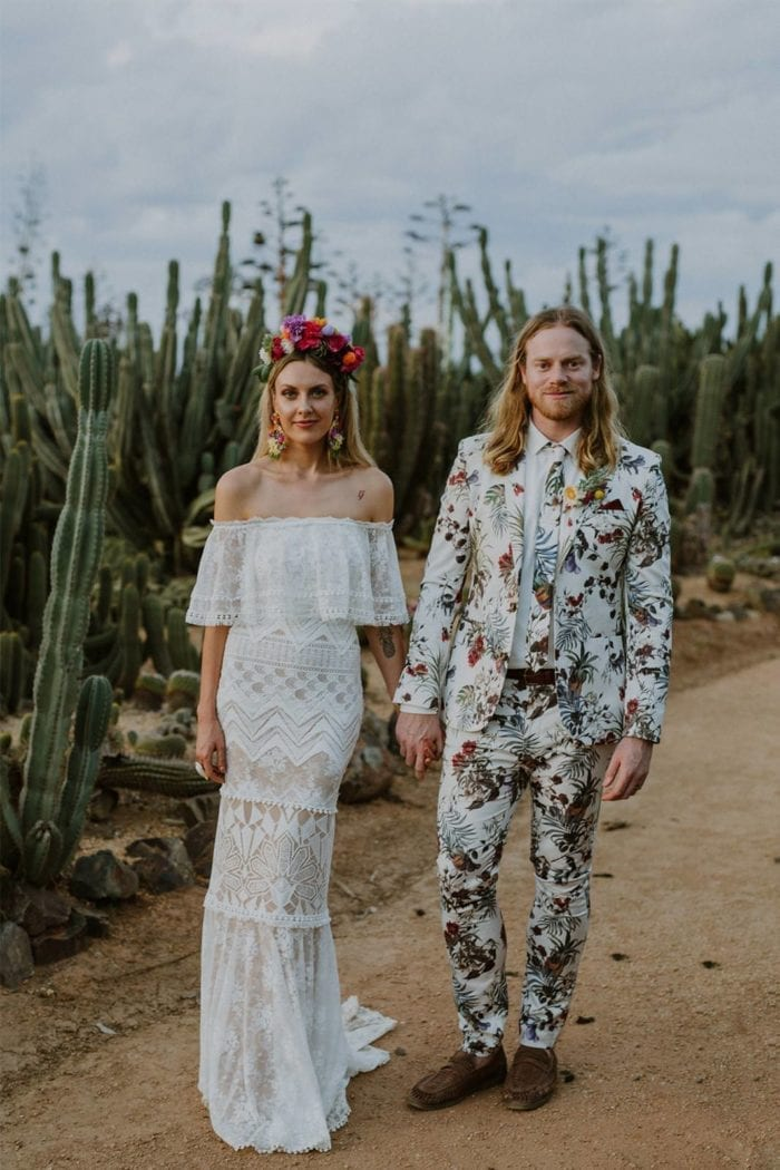 Blonde bride wearing Grace Loves Lace Emanuela Gown holding hands with groom near cacti