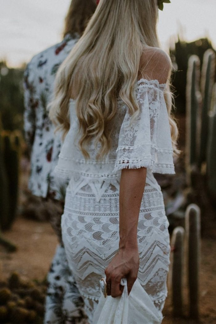 Back shot of bride wearing Grace Loves Lace Emanuela Gown holding skirt in hand