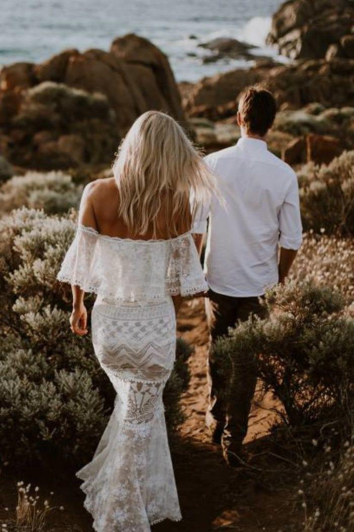 Back shot of blonde bride wearing Grace Loves Lace Emanuela Gown walking with groom