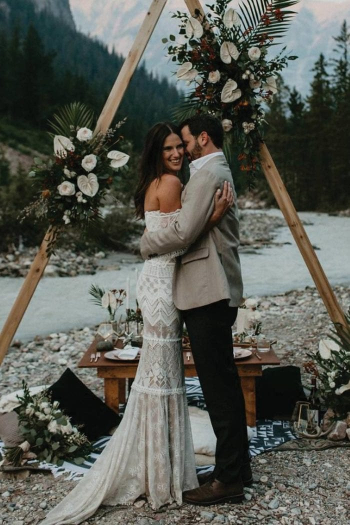 Brunette bride wearing Grace Loves Lace Emanuela Gown being held by groom