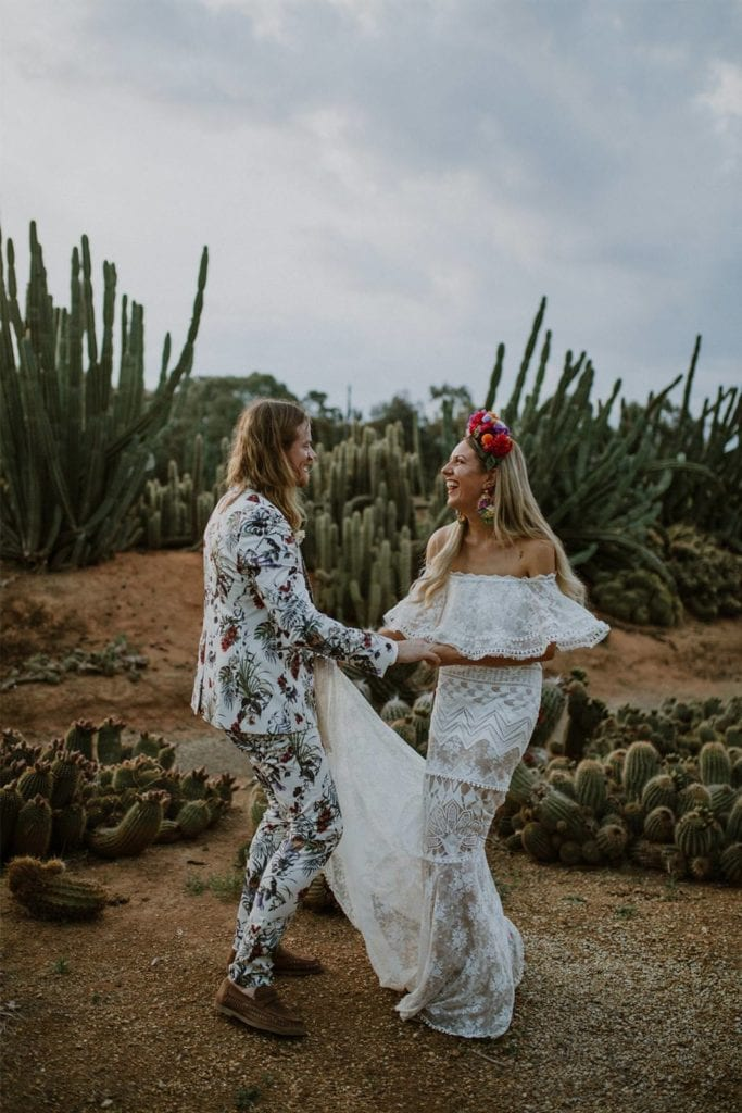 Blonde bride wearing Grace Loves Lace Emanuela Gown dancing with groom surrounded by cacti