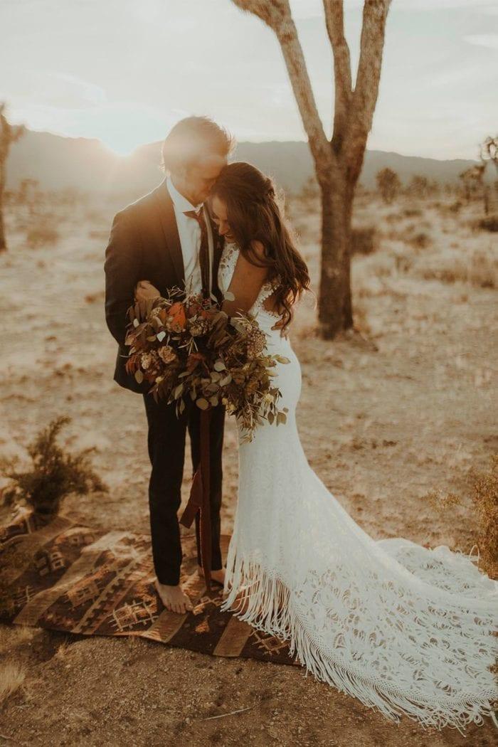 Brunette bride wearing Grace Loves Lace Edie Gown embracing groom