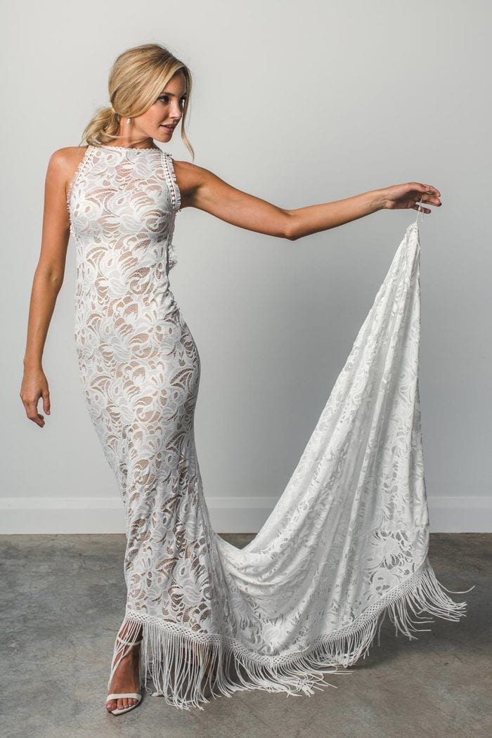 Blonde bride wearing Grace Loves Lace Edie Gown holding train in one hand