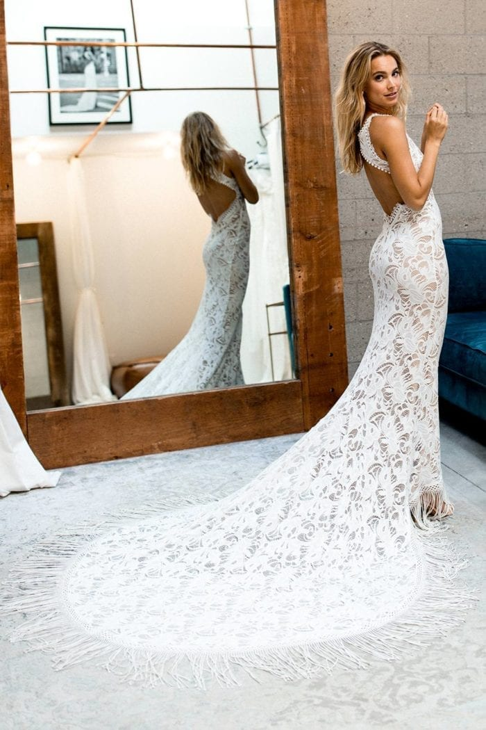 Blonde bride wearing Grace Loves Lace Edie Gown in front of mirror