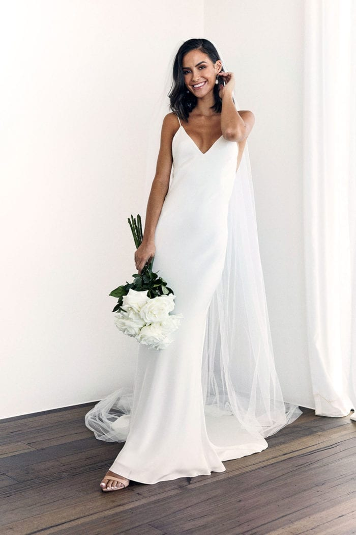 Brunette bride wearing Grace Loves Lace Dove Gown and veil holding bouquet