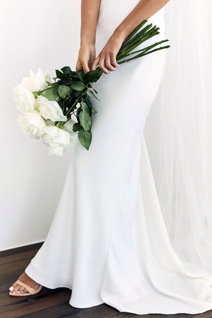 Close-up of bride wearing Grace Loves Lace Dove Gown holding bouquet