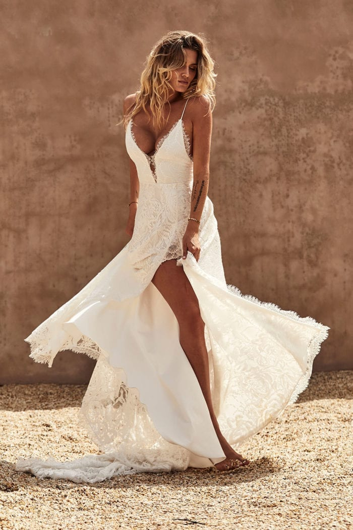 Blonde bride wearing Grace Loves Lace Darling Gown holding skirt in hands