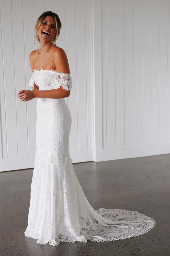 Blonde bride wearing Grace Loves Lace Cien Gown while laughing
