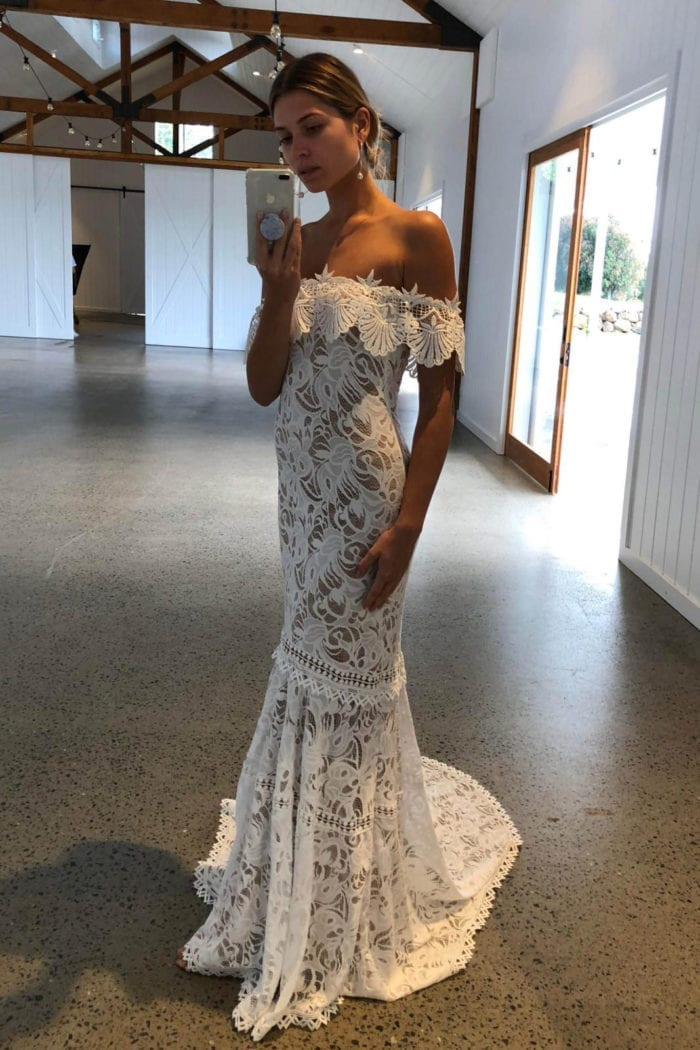 Blonde bride wearing Grace Loves Lace Cien Gown taking photo on phone in front of mirror