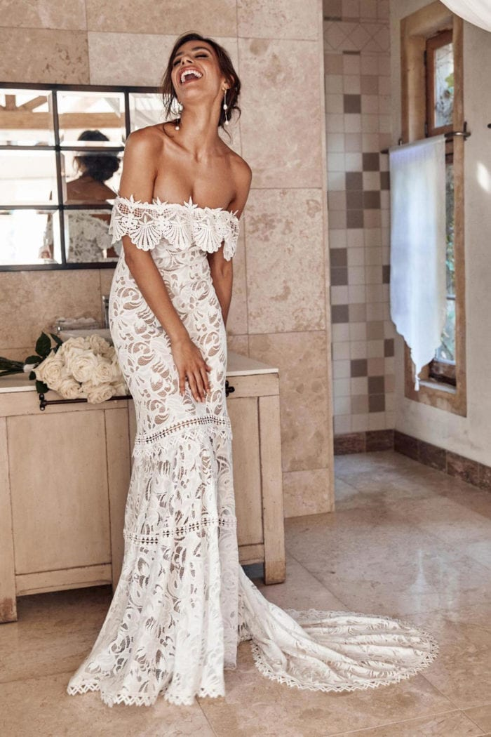 Brunette bride wearing Grace Loves Lace Cien Gown leaning on bench laughing