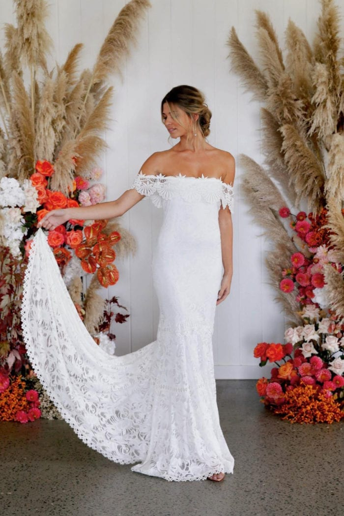 Bride wearing Grace Loves Lace Cien Gown looking to the side with finger in finger loop