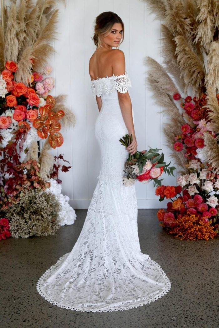 Back shot of bride wearing Grace Loves Lace Cien Gown holding bouquet