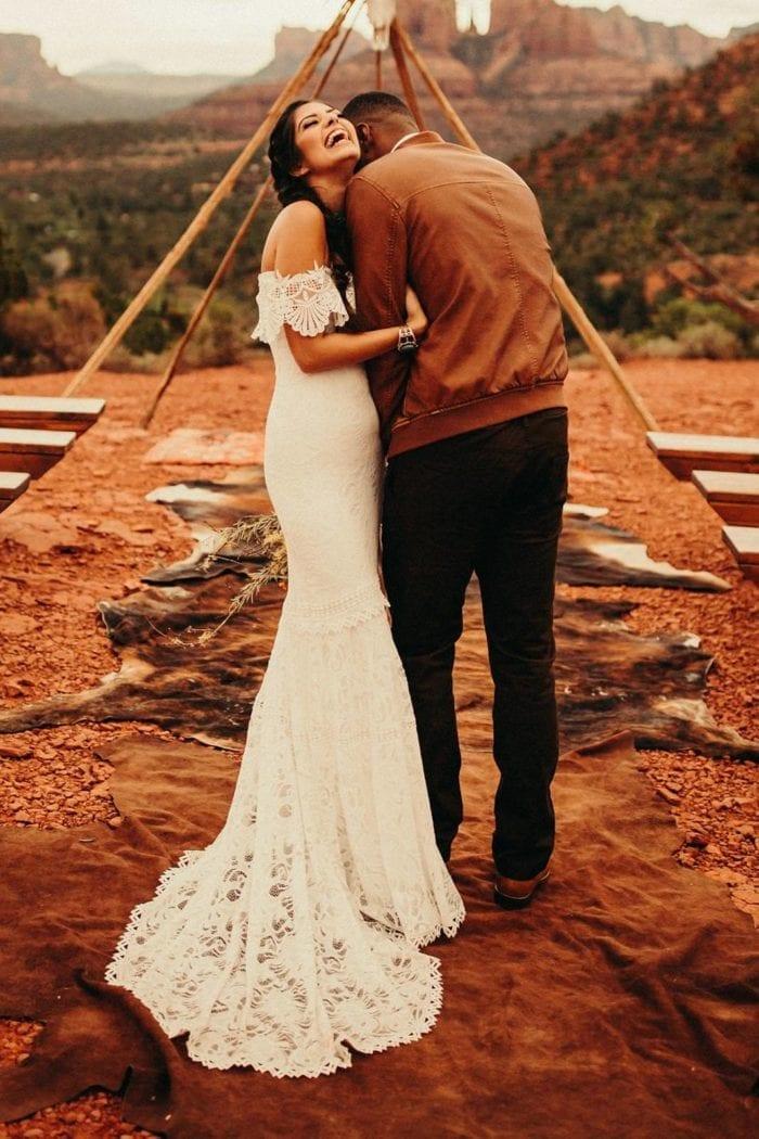 Brunette bride wearing Grace Loves Lace Cien Gown embracing groom