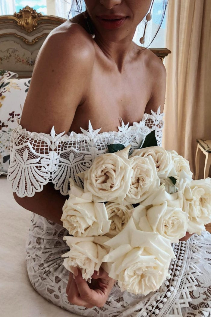 Close-up of bride wearing Grace Loves Lace Cien Gown sitting on bed holding bouquet