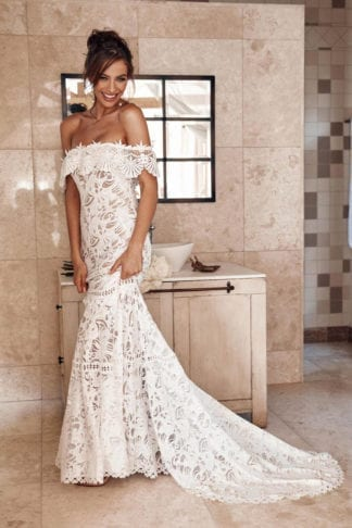Brunette bride wearing Grace Loves Lace Cien Gown holding skirt in hand