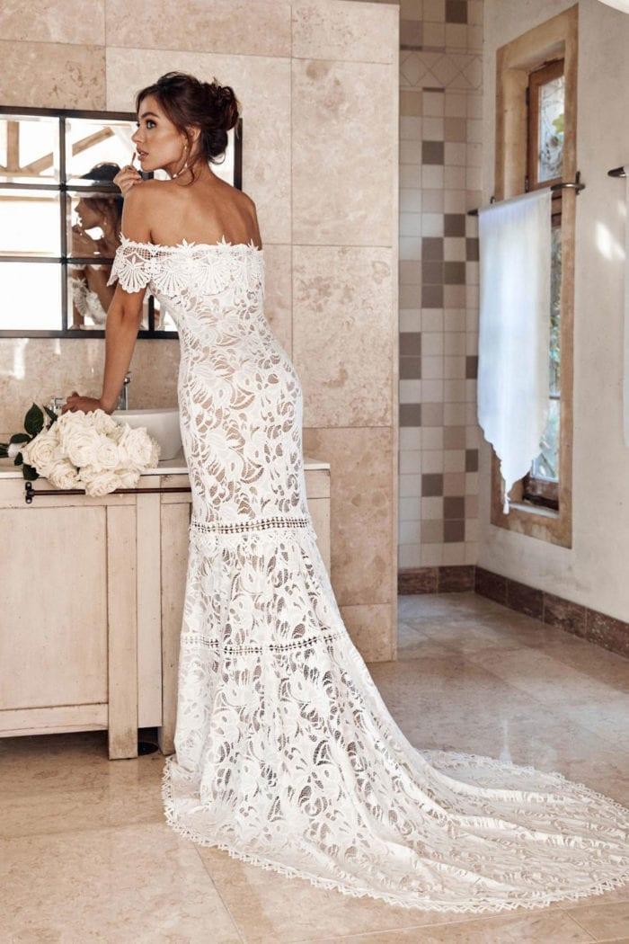 Back shot of brunette bride wearing Grace Loves Lace Cien Gown doing make-up in mirror