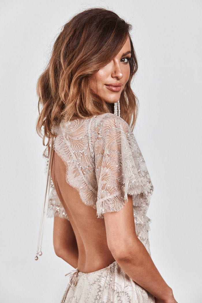Brunette bride wearing Grace Loves Lace Capri Gown looking over shoulder