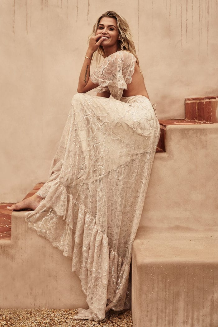 Blonde bride wearing Grace Loves Lace Capri Gown sitting on stairs