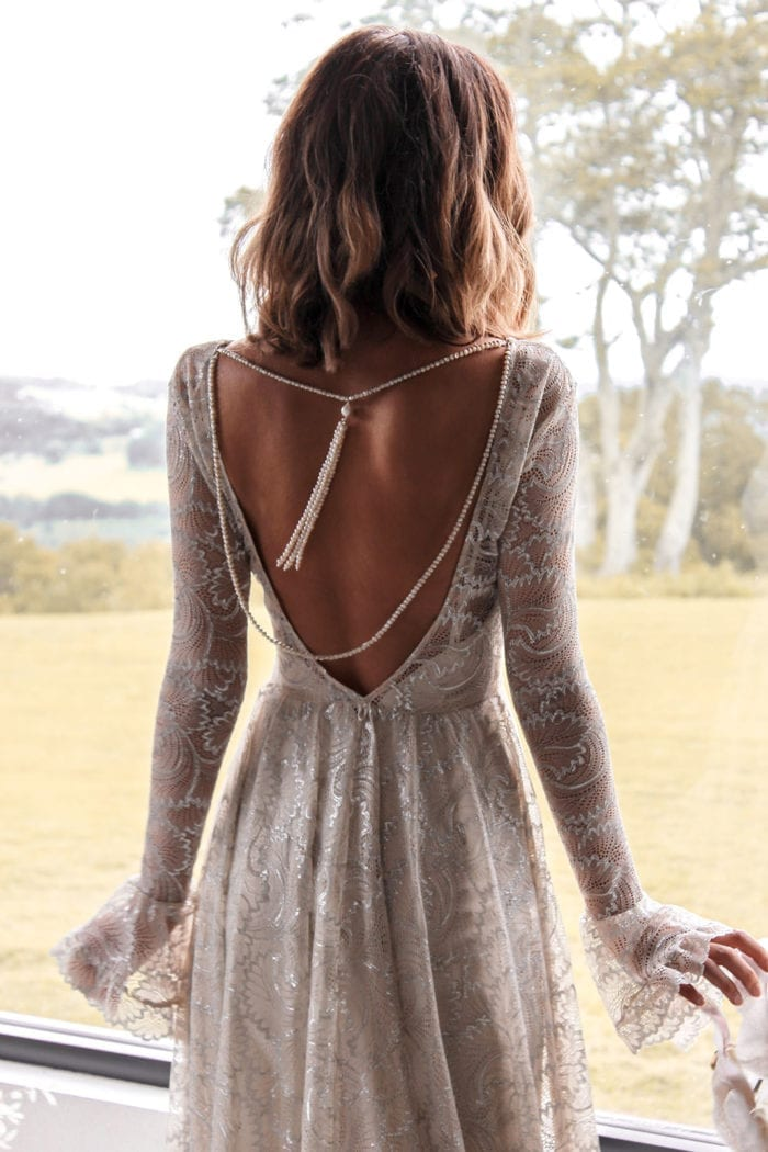 Back shot of bride wearing Grace Loves Lace Bea Gown and backpiece in front of window
