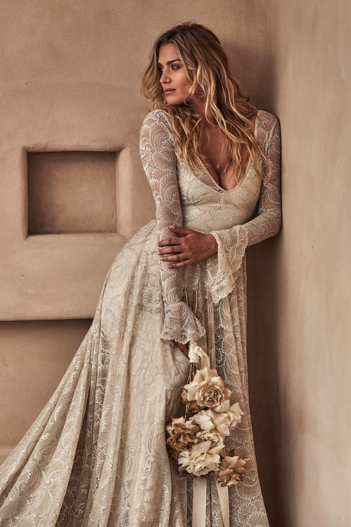 Blonde bride wearing Grace Loves Lace Bea Gown holding bouquet leaning against wall