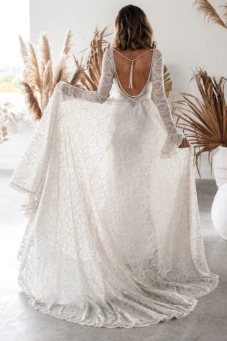 Brunette Back shot of bride wearing Grace Loves Lace Bea Gown holding skirt in hand
