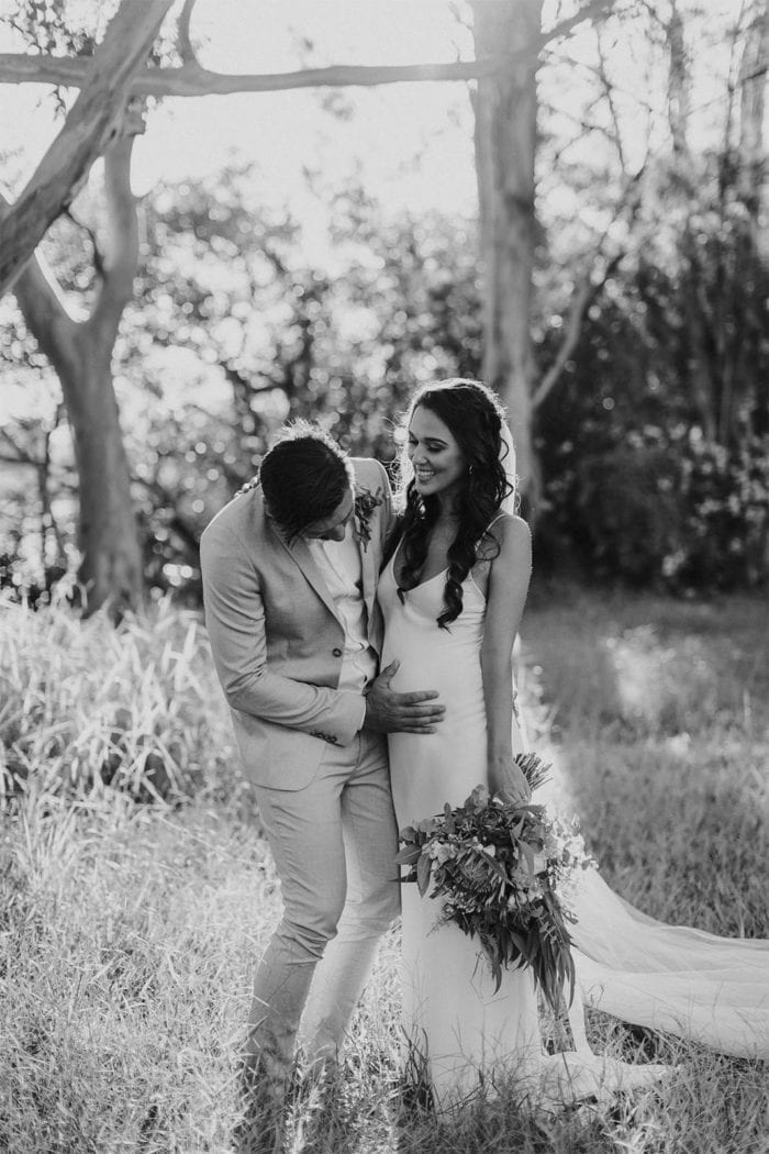 Black and white shot of bride wearing Grace Loves Lace Arlo Gown holding bouquet with groom touching belly