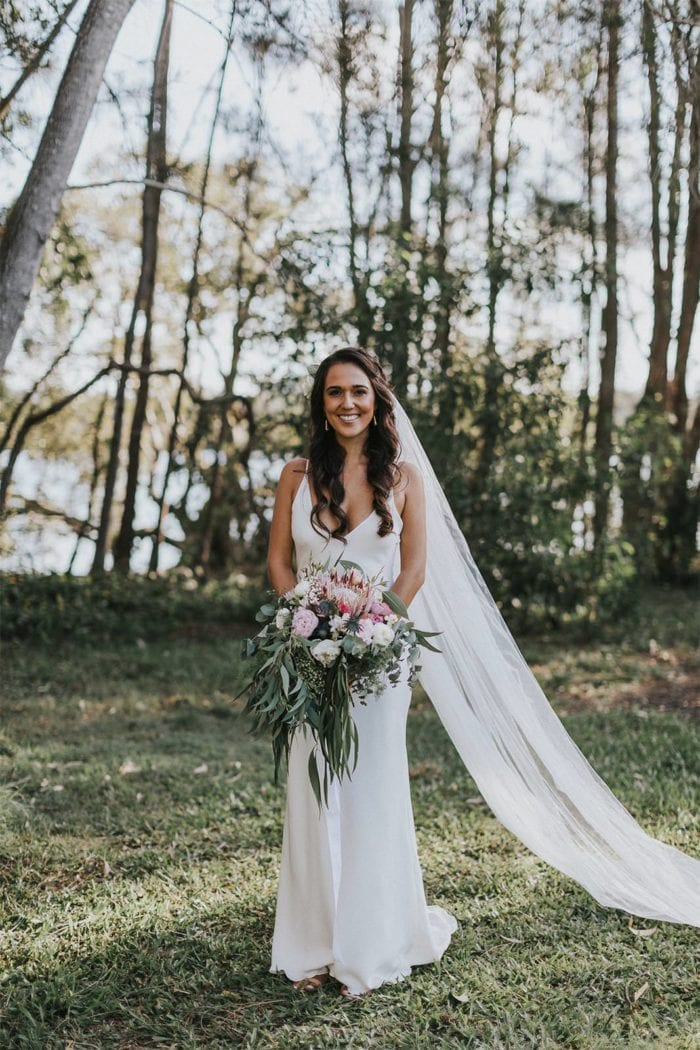 Brunette bride wearing Grace Loves Lace Arlo Gown holding bouquet