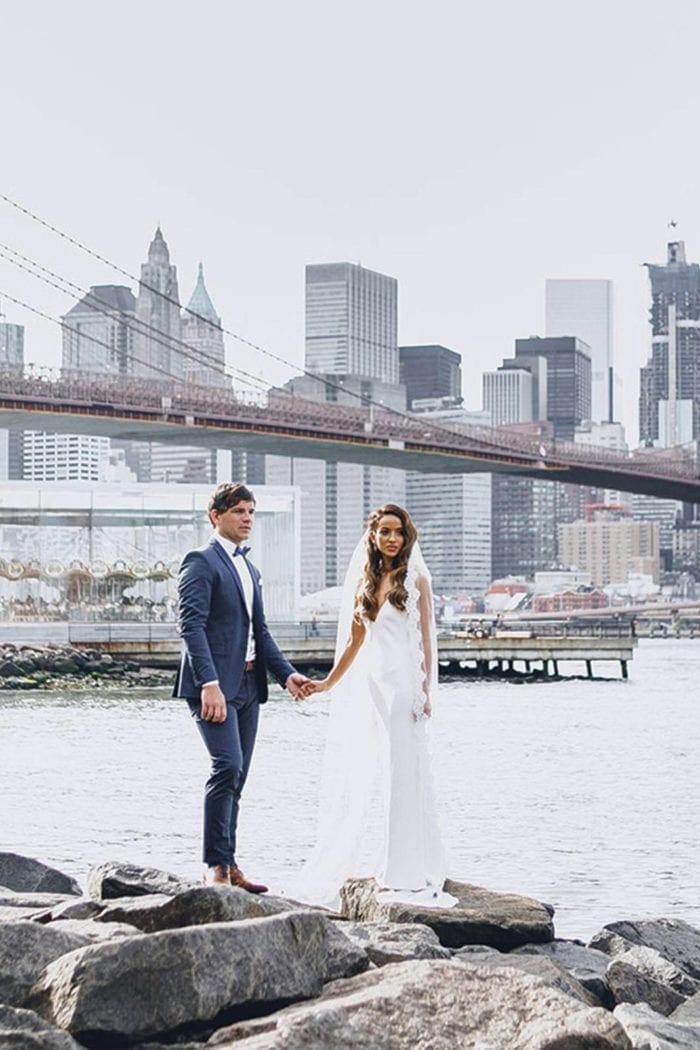 Brunette bride wearing Grace Loves Lace Arlo Gown holding hands with groom on rocks near river
