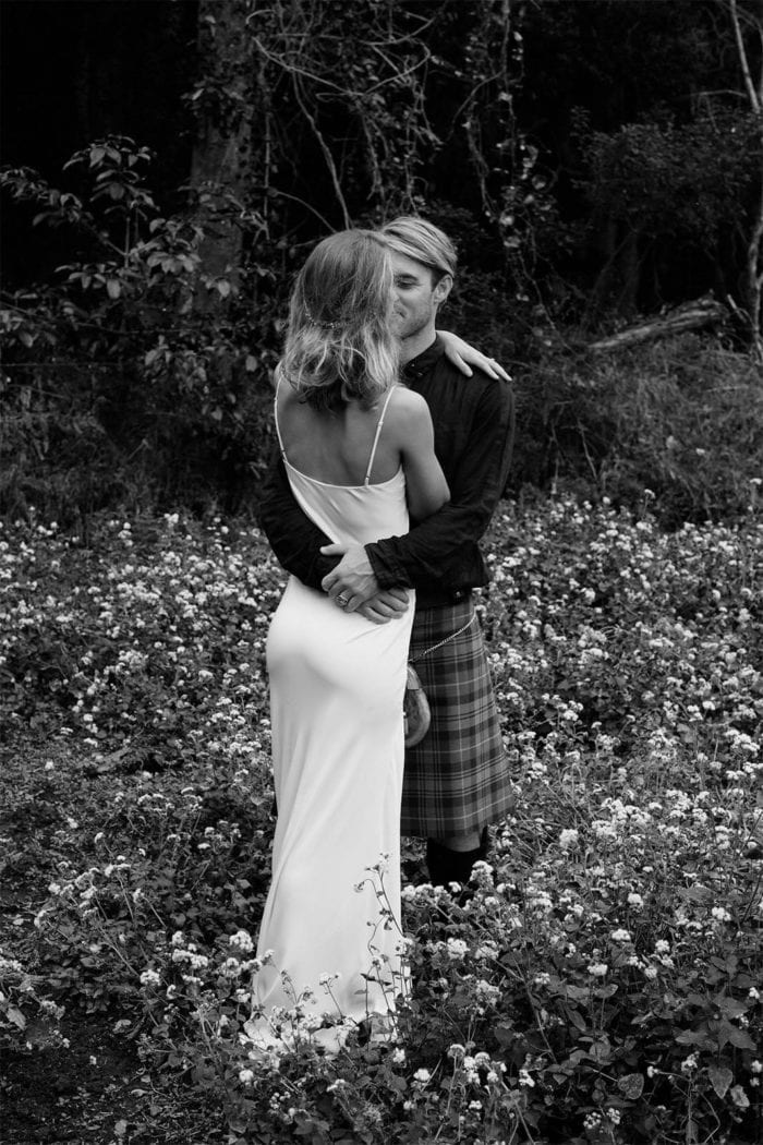 Black and white shot of bride wearing Grace Loves Lace Arlo Gown embracing groom in kilt