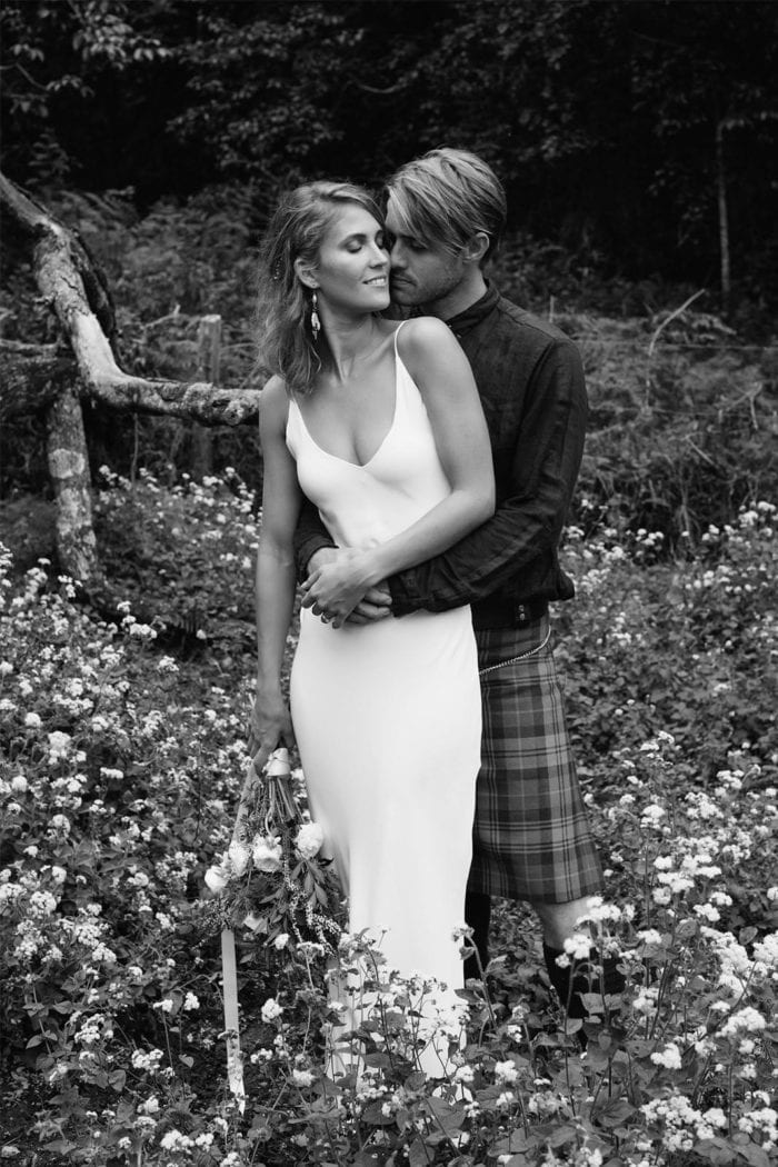 Black and white shot of bride wearing Grace Loves Lace Arlo Gown holding bouquet embracing groom in kilt