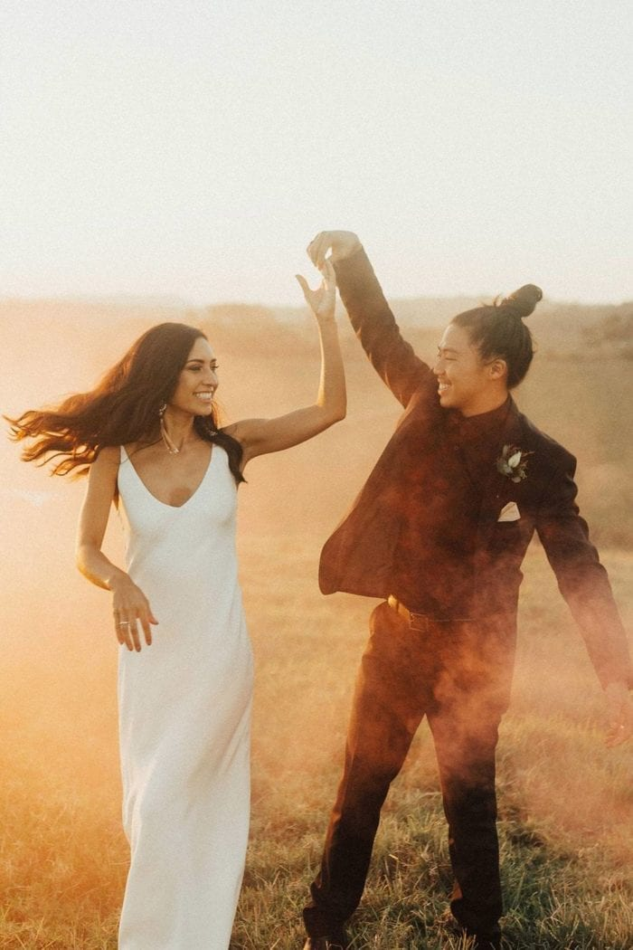 Brunette bride wearing Grace Loves Lace Arlo Gown dancing with groom in dusty field